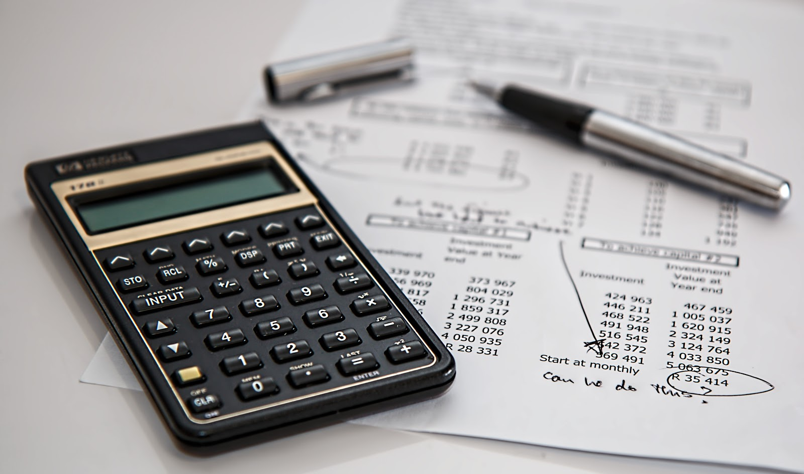 black-calculator-near-ballpoint-pen-on-white-printed-paper-detailing-finances