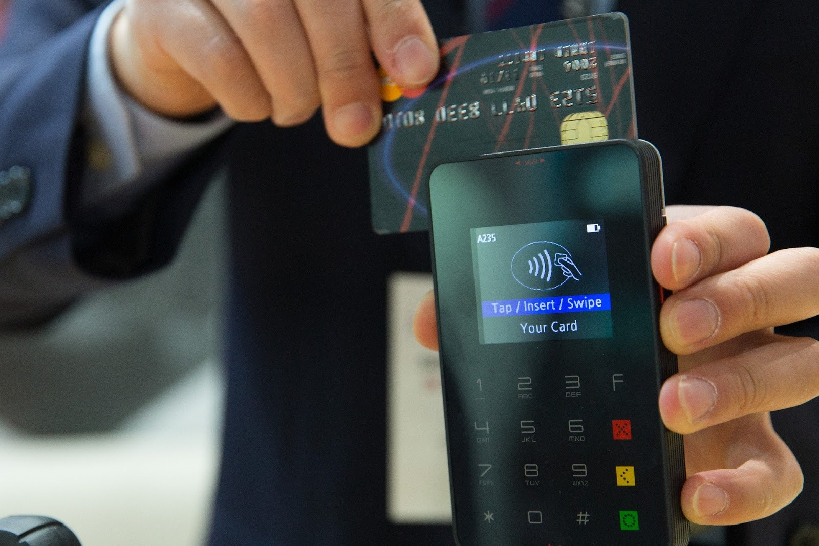 man-scanning-bank-card-through-card-reader