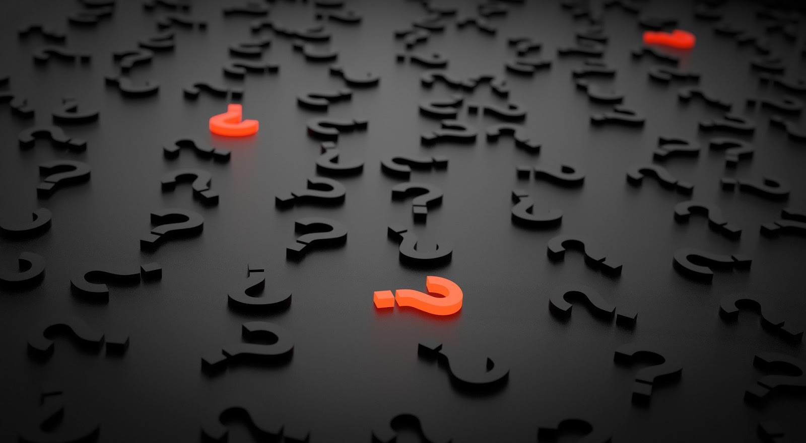black-and-orange-question-marks-on-a-dark-grey-surface-graphic