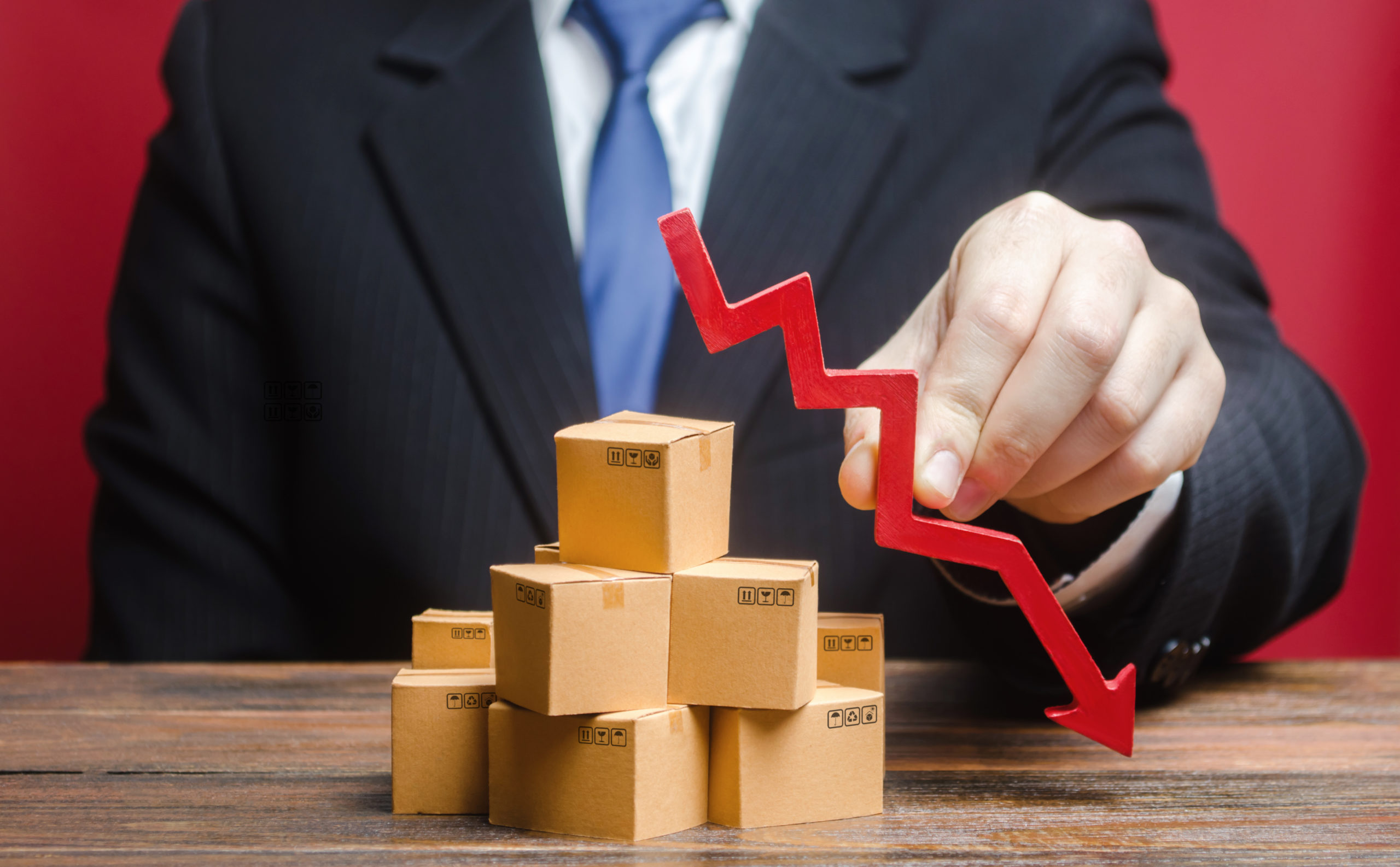 businessman-holding-a-red-arrow-pointing-down-above-boxes-stack-pile