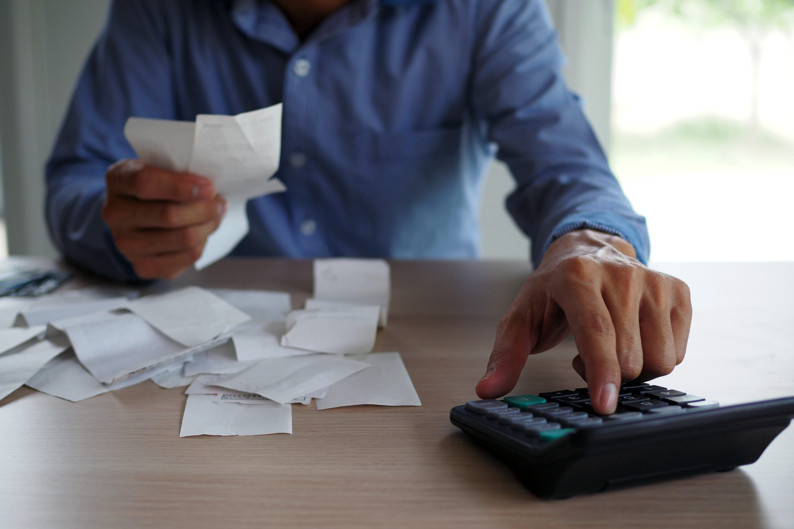 businessman-using-calculator-and-receipts-to-figure-his-merchant-cash-payments