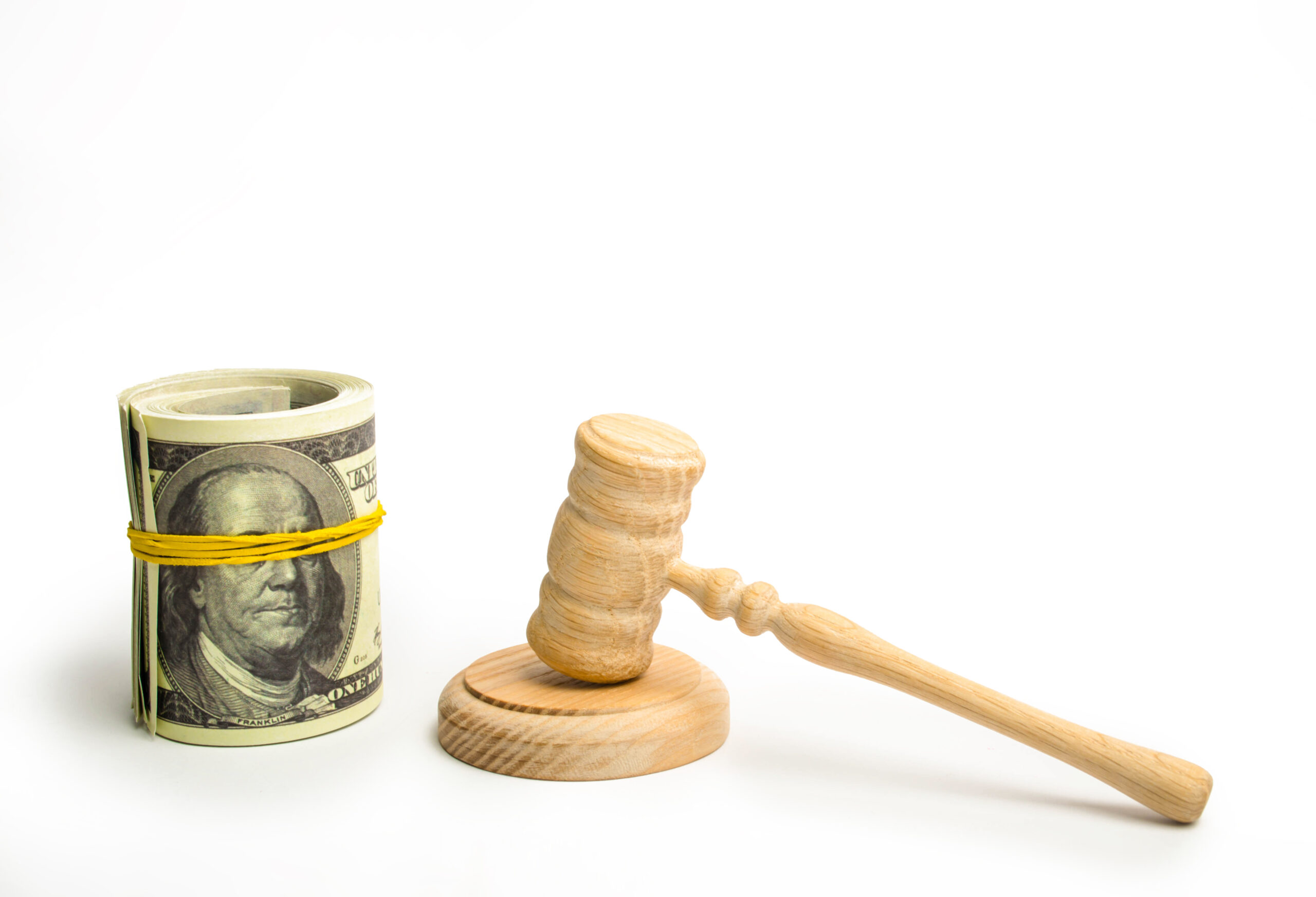 wooden-gavel-next-to-bundle-of-american-hundred-dollar-bills-held-in-roll-by-a-rubber-band