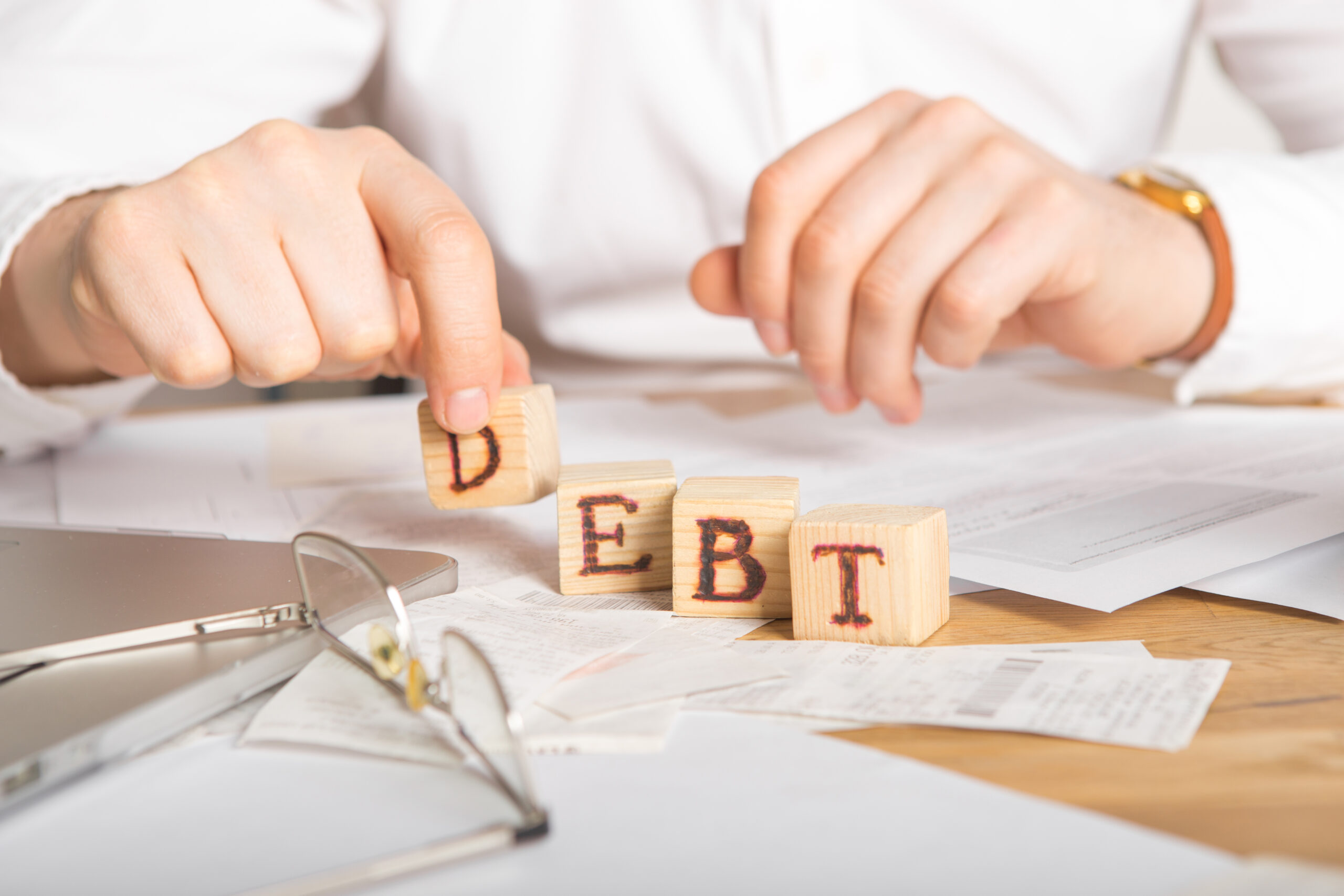 businessman arranging wooden blocks with letters to spell the word debt