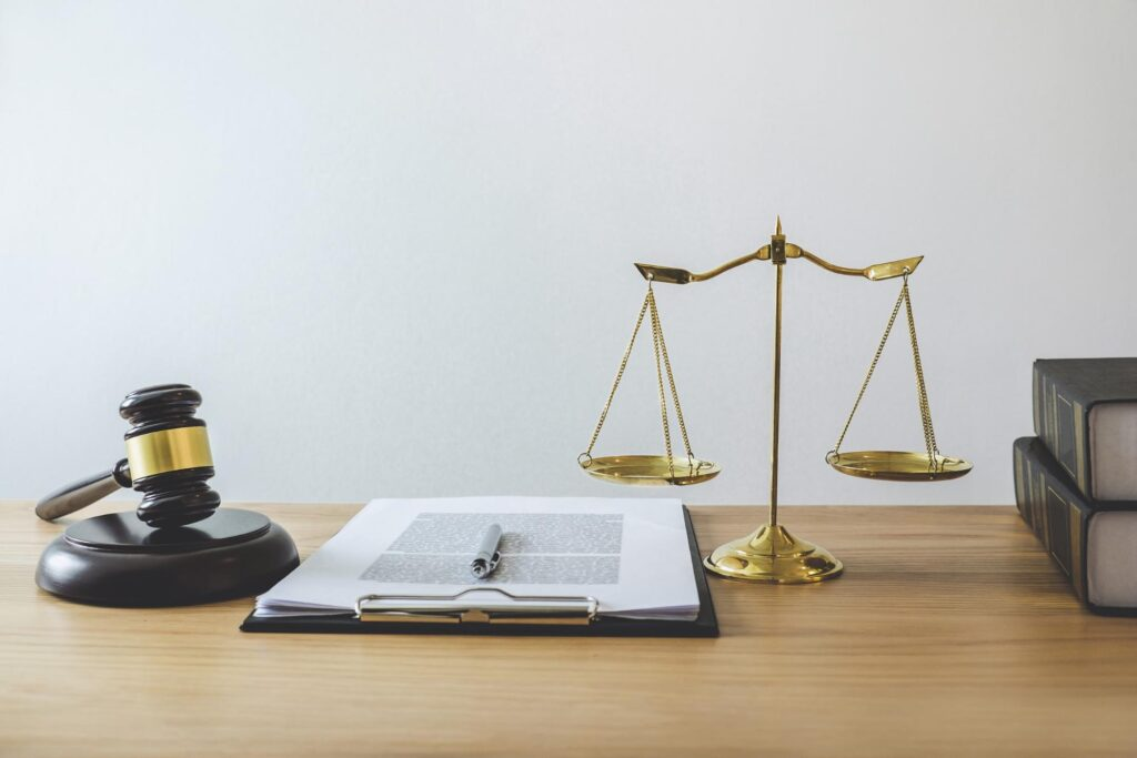 a gavel, scales of justice, and legal forms on the desk of an attorney
