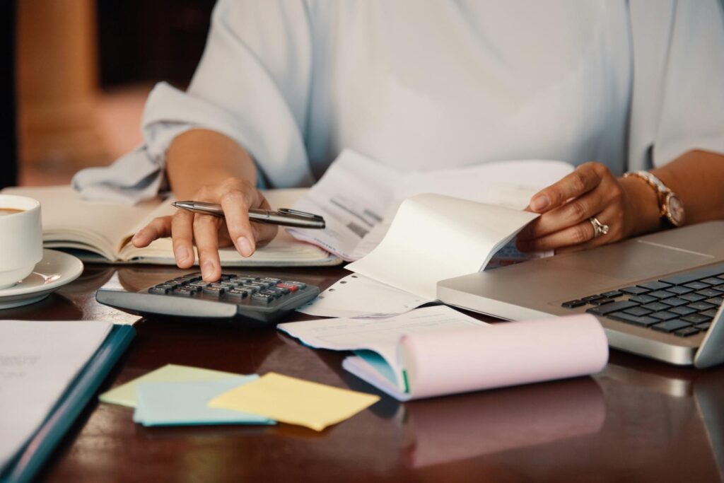 A business owner struggling with debt from a merchant cash advance goes over her bills to make sense of her accounting books.