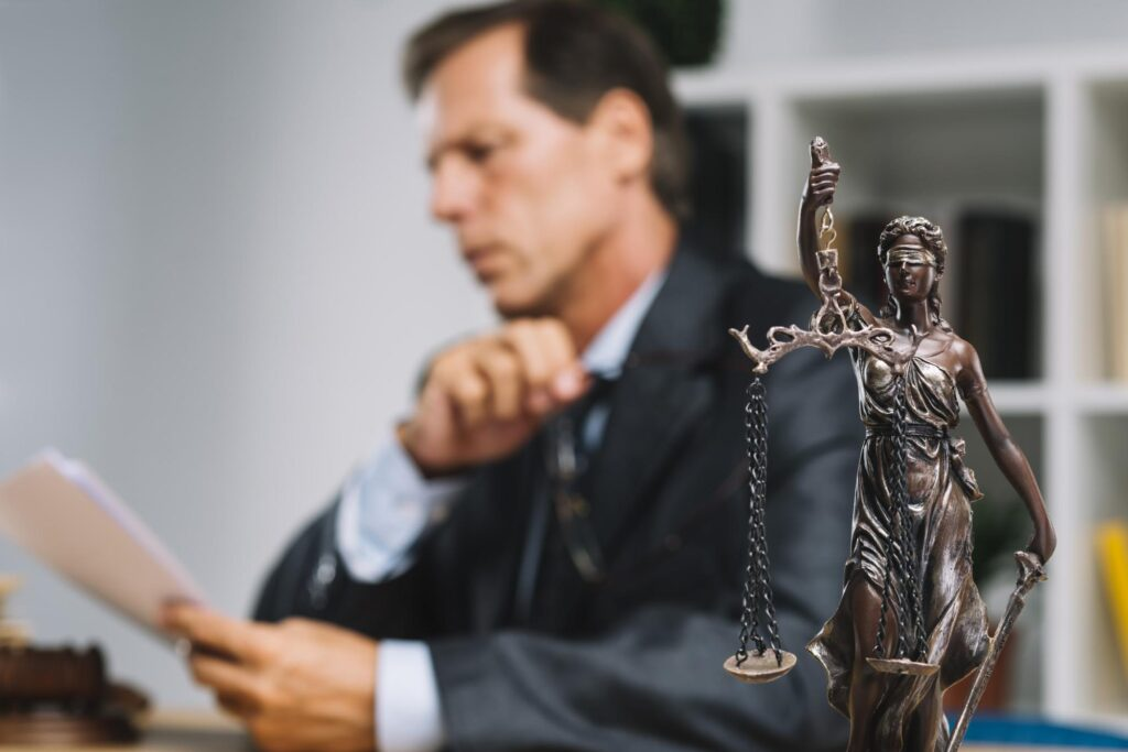 A merchant cash advance attorney reviews a client's advance agreement with the statue of justice in the foreground of the image.
